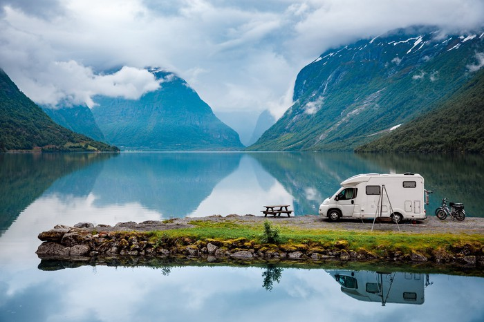 RV parked on a lake promontory amid mountains.