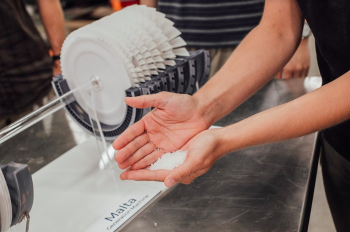 A person holding salt in their palm in front of a device with the Malta name on it