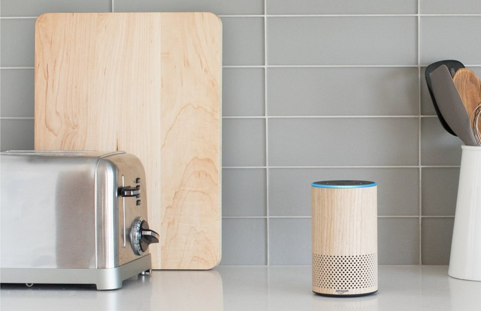 Echo sitting on a kitchen counter next to a toaster, a wooden cutting board, and a crock holding cooking utensils