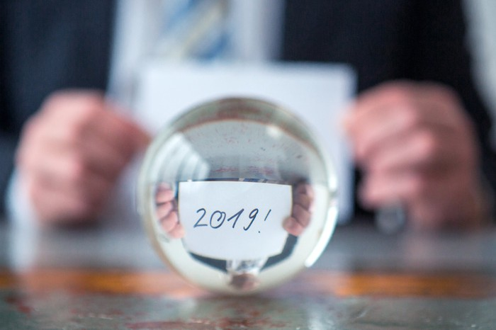 Man holding card with 2019 written on it behind a glass ball.