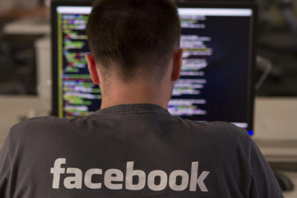 A Facebook employee entering code on his computer.