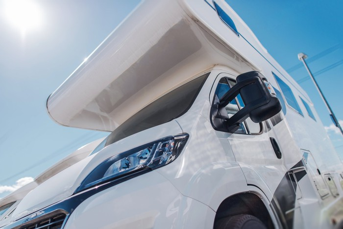 Close-up view of a white camper van in lot under bright sun.