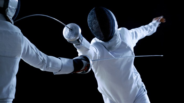 Two fencers facing off against each other in a dark room.