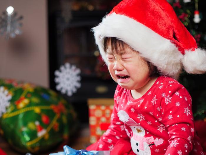 Child wear Santa hat crying