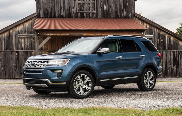 A blue Ford Explorer, a midsize crossover SUV, parked in front of a barn.