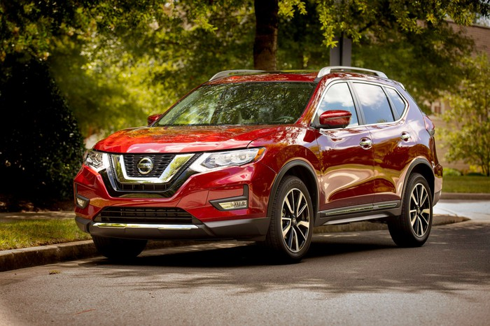 A red Nissan Rogue, a compact crossover SUV. parked on a leafy street.