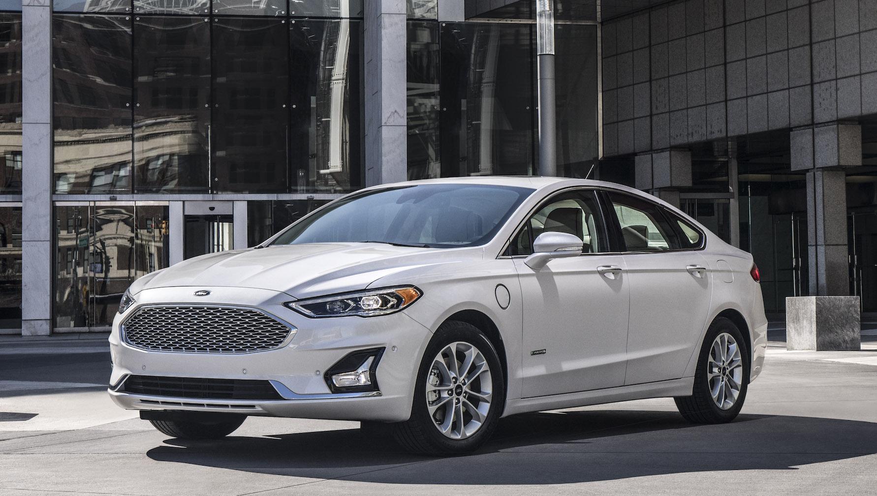 A white Ford Fusion Hybrid, a midsize sedan.