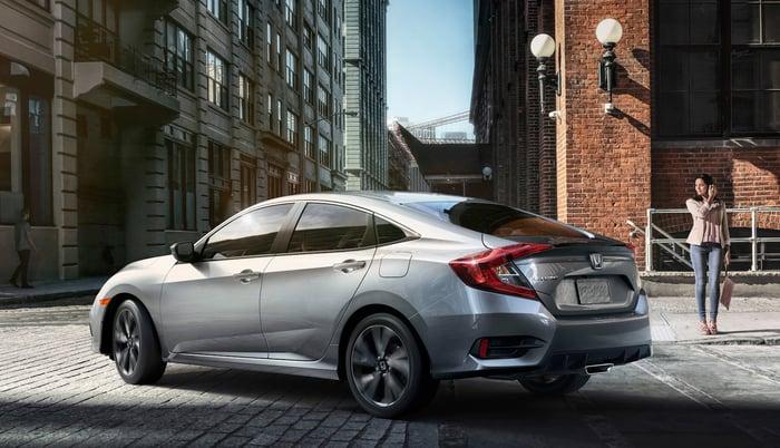 A silver Honda Civic, a compact sedan, on a city street.