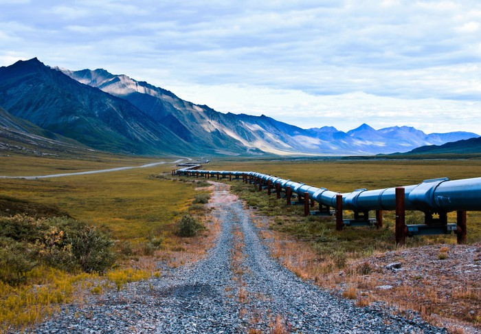 Pipeline running alongside a gravel road with mountains in the background