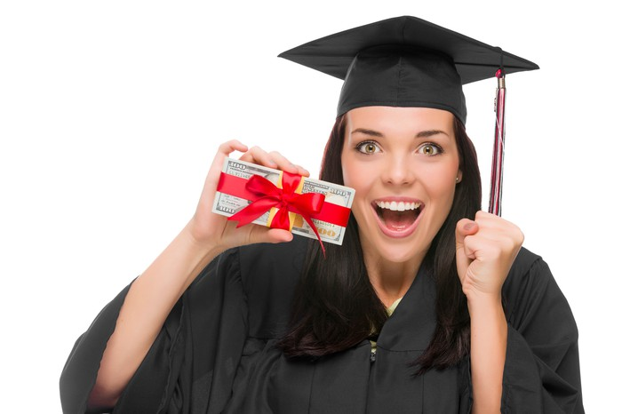 Woman in graduation attire holding giftwrapped cash