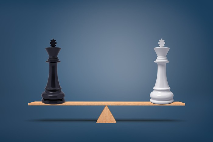 Two chess piece kings on opposite ends of a scale