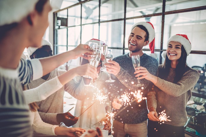 Workers toast with glasses at a holiday party.
