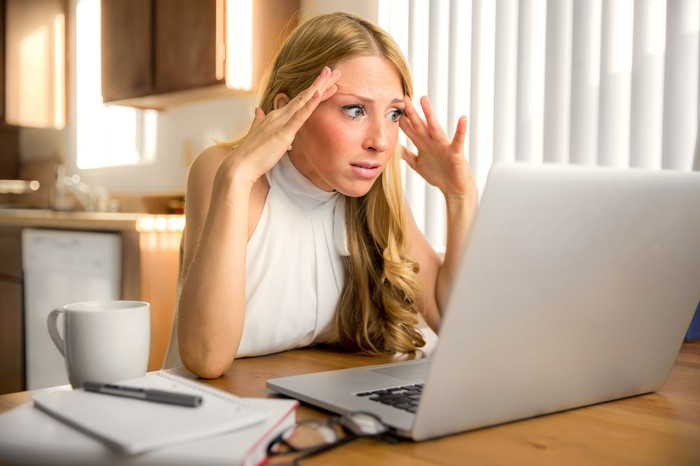 Woman at laptop holding her hands to her head and staring as if in shock
