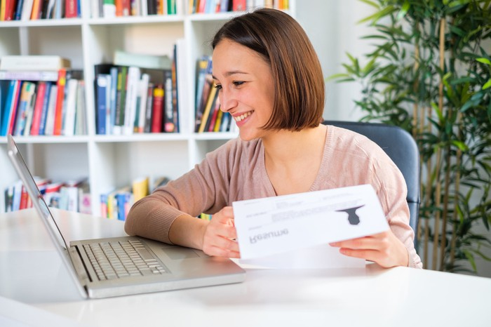 Woman at laptop smiling and holding document