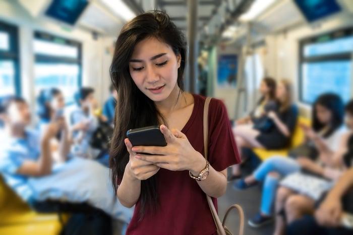 A woman using a smartphone while riding mass transit.