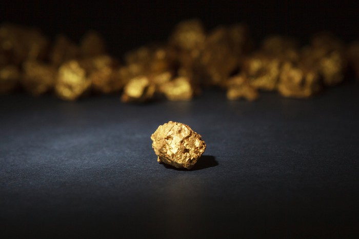 Single gold nugget in foreground, with many gold nuggets in background.