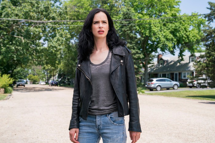 A woman in jeans and a black leather jacket stands in the street looking bewildered.