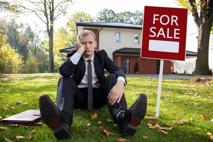 Unhappy man in suit sitting on lawn in front of a house and next to a for sale sign.