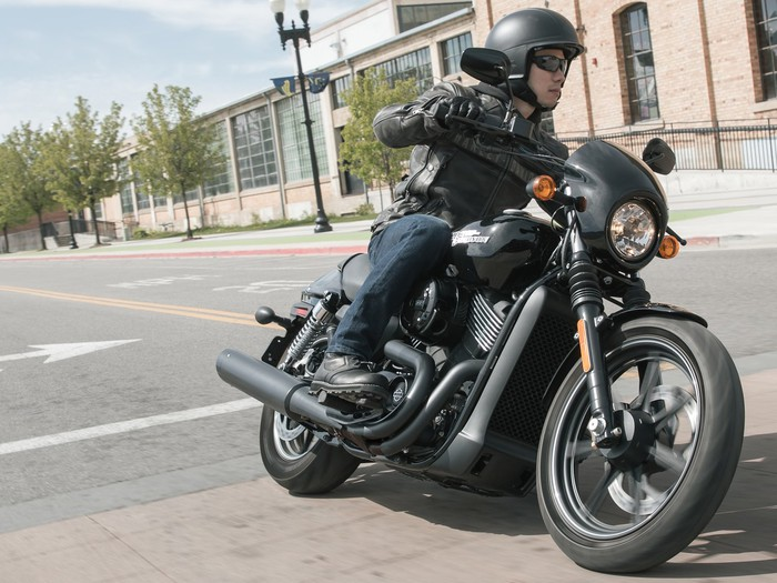 A person riding a Harley-Davidson Street 750 motorcycle on a city street.