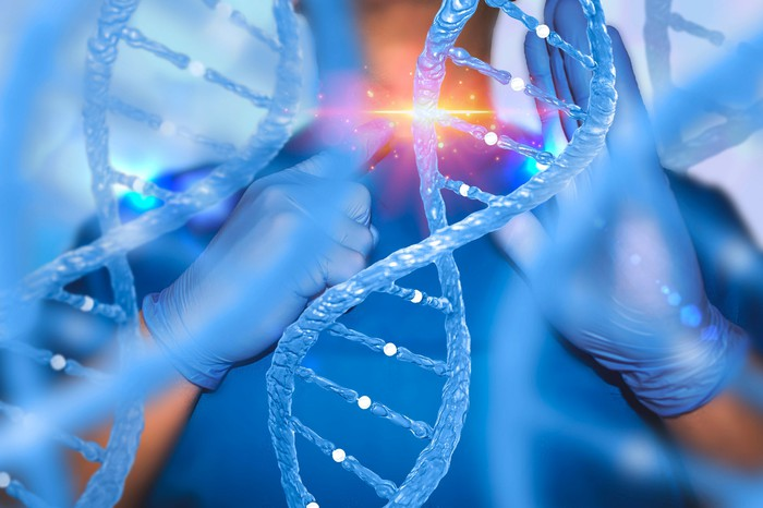 Large image of DNA helix with physician standing behind it holding his finger up to a strand with a bright light appearing on it