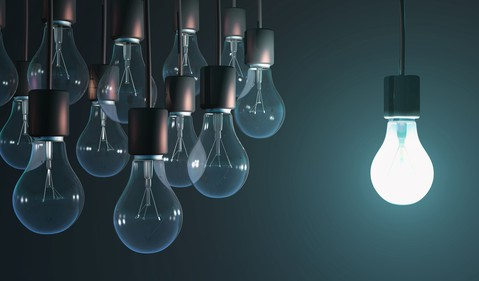 bright light bulb shining near group of unlit bulbs contrarian different stand out