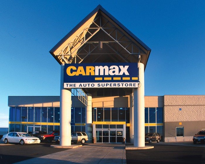 Two-story building with CarMax triangular carport on columns in front, with several vehicles nearby.