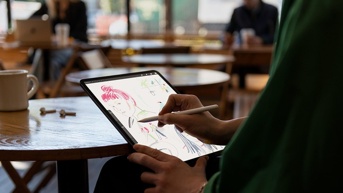 Person in a coffee shop drawing on iPad Pro