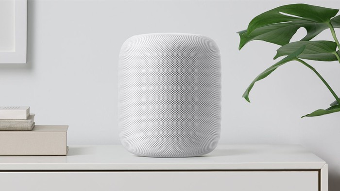 A white HomePod sitting on a dresser surrounded by books and a plant.