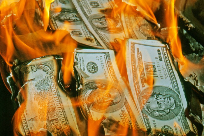 Piles of hundred and twenty dollar bills engulfed in flames.