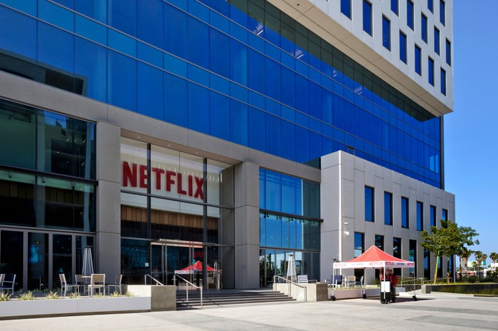 A steel and glass building with the Netflix logo above the door.