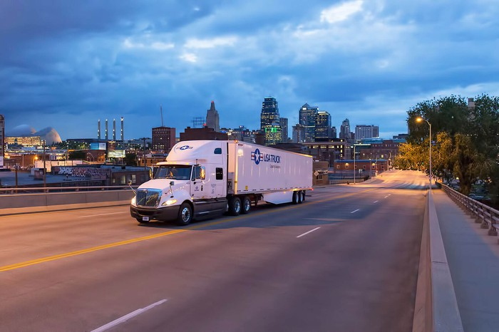 A USA Truck tractor trailer drives in front of a city skyline.