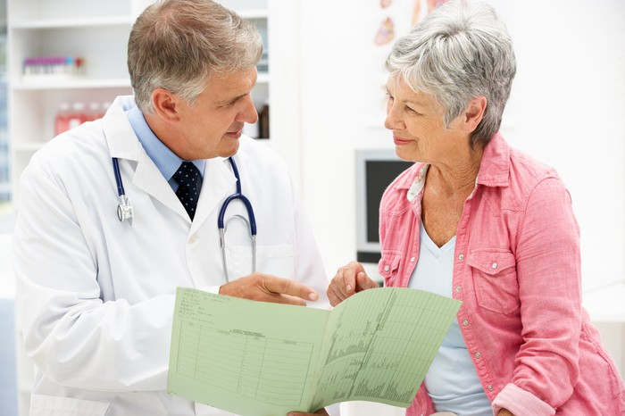A physician going over medical test results with a senior woman.