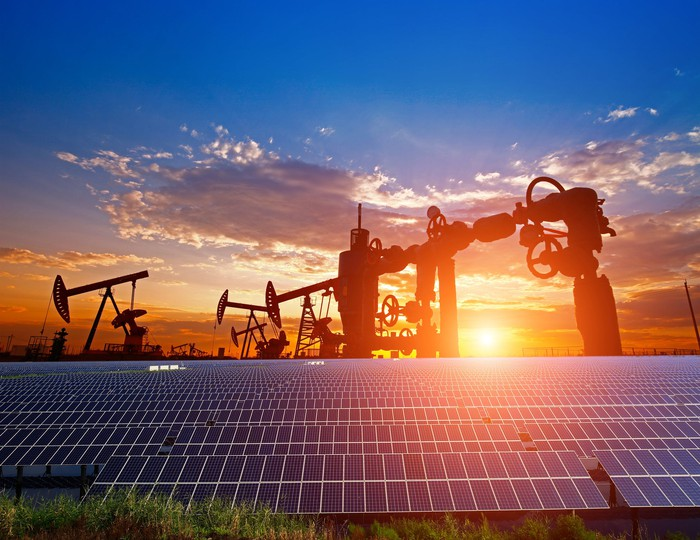 Oil pumps, a natural gas well, and solar panels with the sun setting in the background