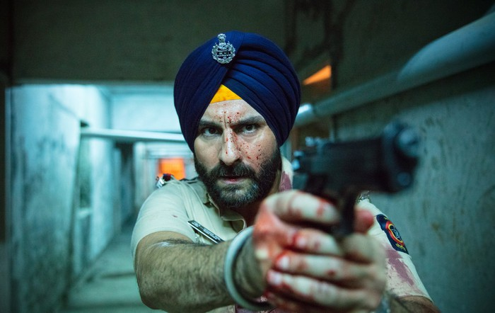 A man wearing a turban pointing a gun with his face and hands covered in blood spatter.