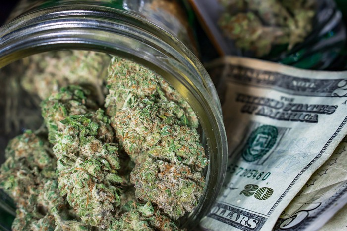 A tipped-over jar filled with dried cannabis buds lying atop a messy pile of cash bills.