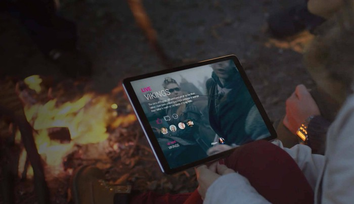 A person holding a tablet displaying a mockup of T-Mobile's TV app while sitting next to a campfire.