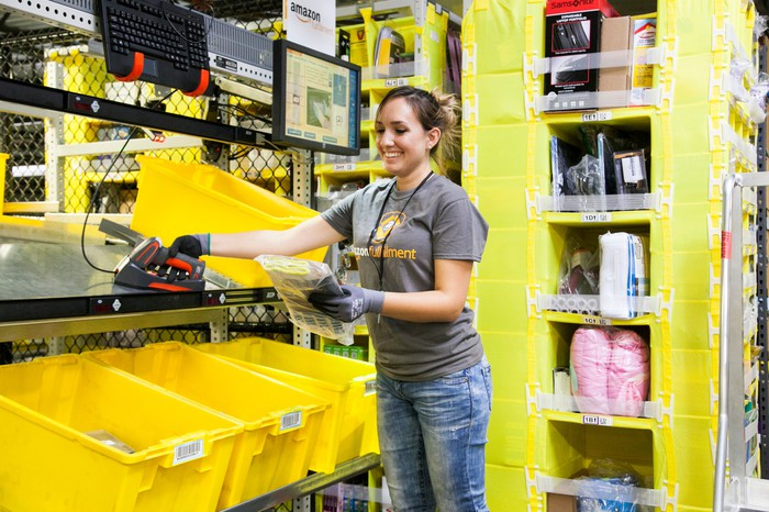 An Amazon fulfillment employee surrounded by bright yellow bins preparing a package for shipping.