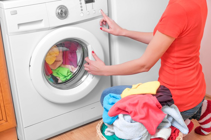 A woman changing the settings on a washing machine, with a basket of laundry to her left.