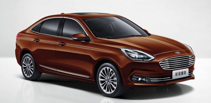 A 2019 Ford Escort, a brown compact sedan, with Chinese-language license plates.