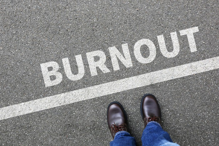 A person stands on a line that says burnout.