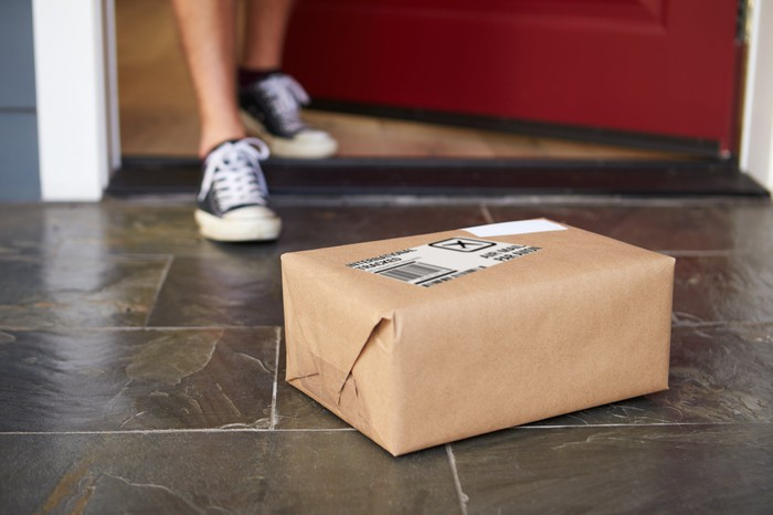 A parcel wrapped in brown paper sitting on a doorstep.
