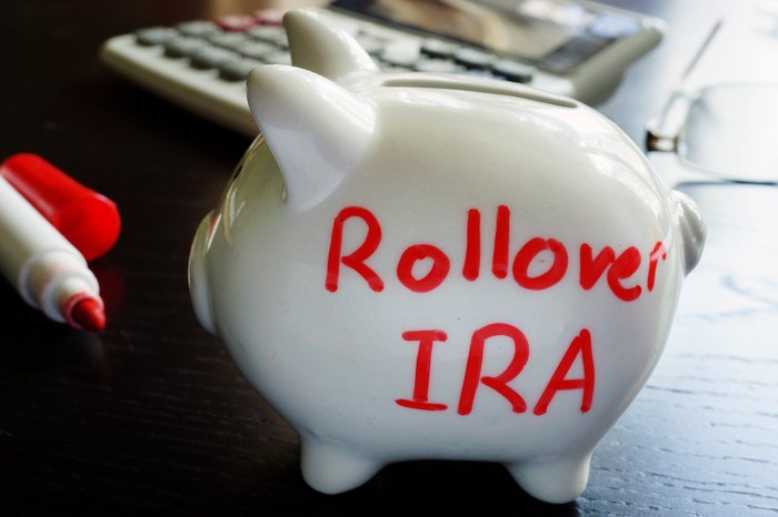 A piggy bank with the words Rollover IRA in red, with an uncapped red marker and a calculator next to it.