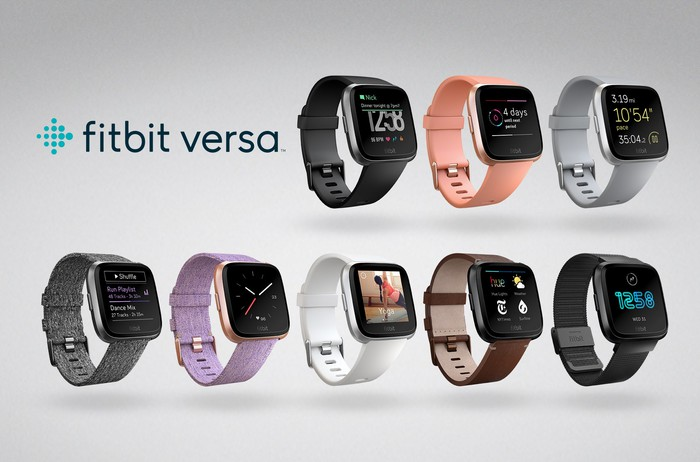 Eight Fitbit Versa smartwatches in different color combinations