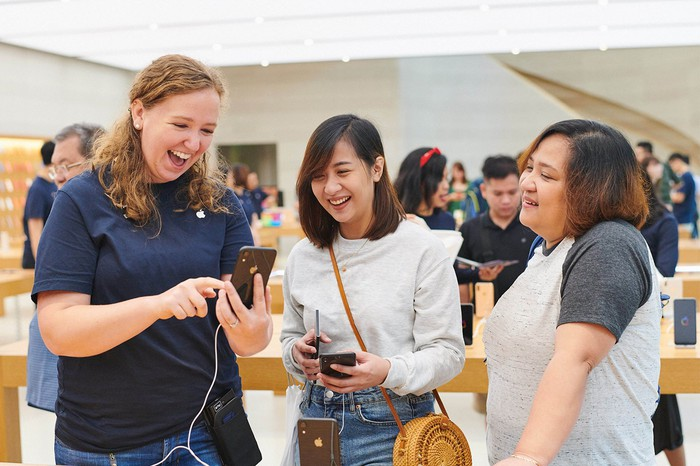 Customers using an iPhone XR at an Apple Store