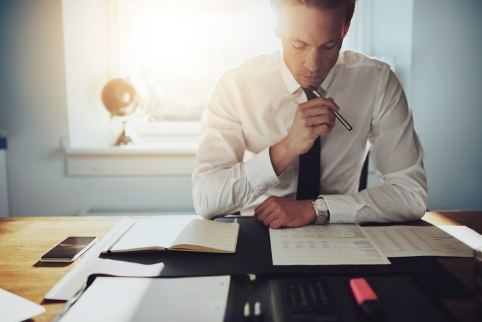 Man in white shirt and tie looking at financial paperwork on desk.