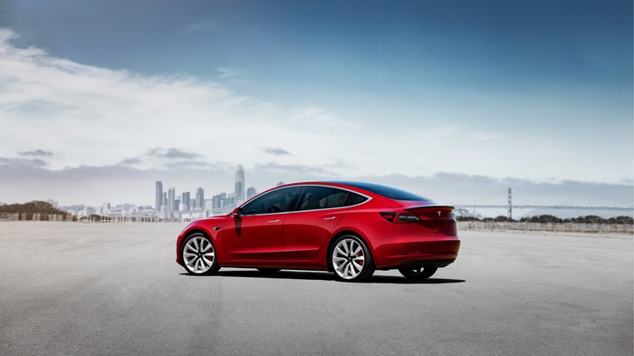 Red Model 3 with a city skyline in the background