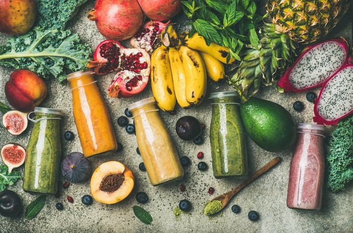 An assortment of colorful bottled smoothies surrounded by fruit and vegetables on a wood table.