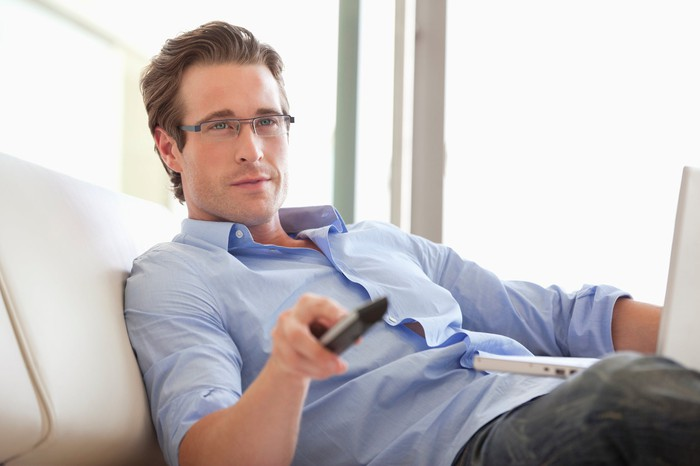 A man holding up a remote and watching TV, with a laptop in his lap