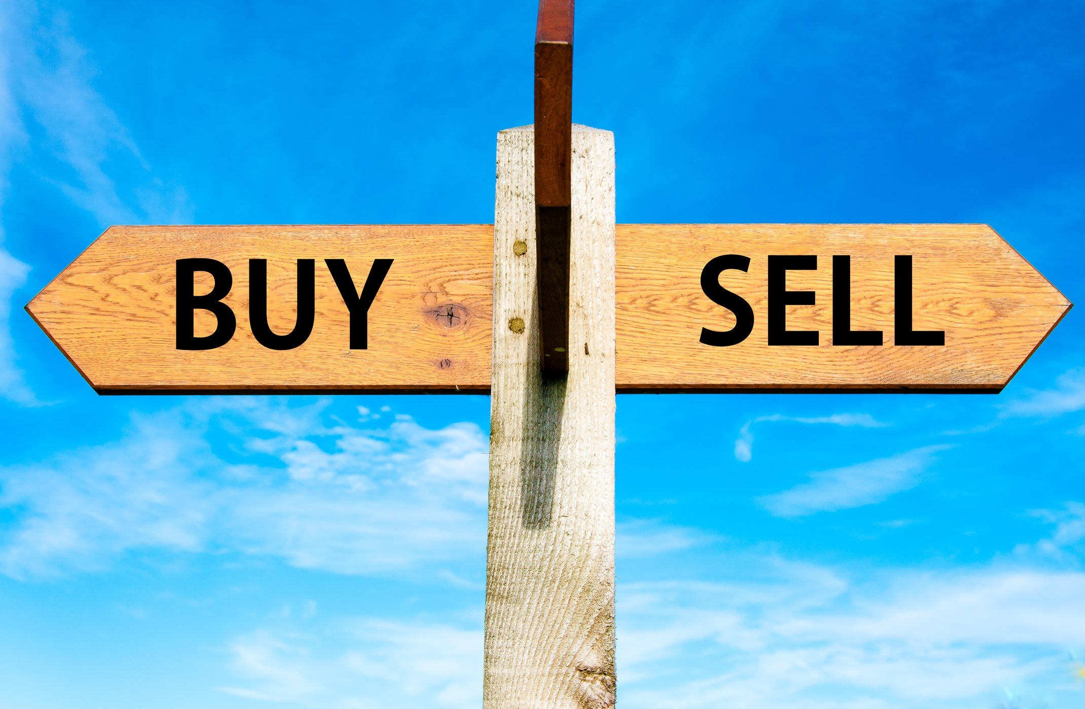 A sign with pointing arrows at each end labeled buy on one side and sell on the other.