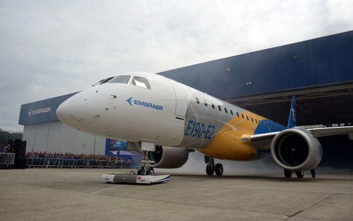 An E190-E2 in Embraer livery in front of an aircraft hangar.